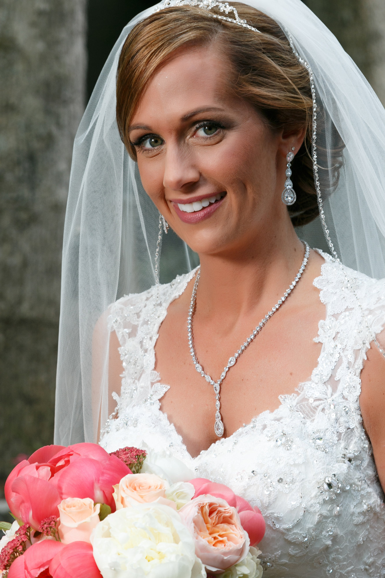 Melissa smiles in wedding gown with bouquet