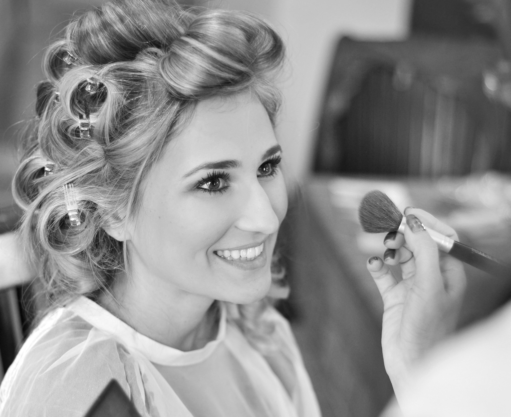 happy bride getting hair and makeup professionally done