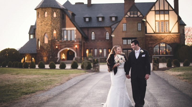 Bride and groom arm in arm in front of Dover Hall Estate