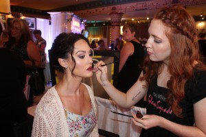 Alex finishes up makeup for a model in a bridal fashion show.
