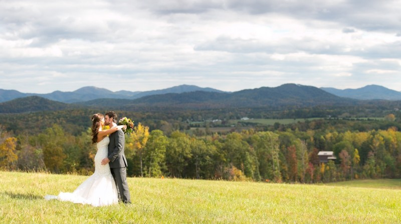 bride and groom embrace with mountainous backdrop